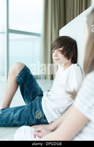 Teenage boy sitting on floor looking out window Banque D'Images