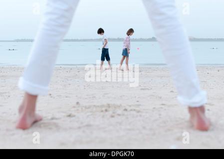Girl standing on beach, à regarder ses frères et sœurs au bord de l'eau Banque D'Images