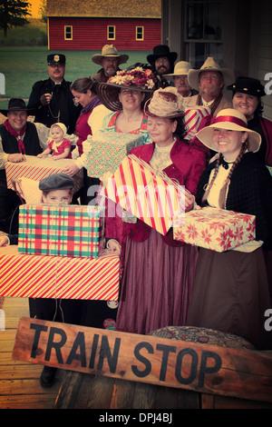 Vintage d'un groupe de personnes à l'ancienne en attente à l'arrêt de train avec des cadeaux de Noël