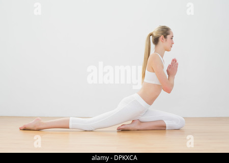 Ponytailed calme woman doing yoga pose sitting on floor Banque D'Images