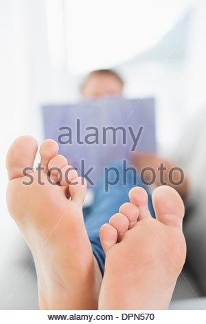 L'homme trouble de la lecture d'un livre avec l'accent sur les pieds nus Banque D'Images