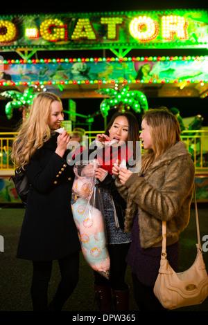 Trois jeunes adolescentes les amis des jeunes femmes s'amusant eating Cotton Candy candyfloss, à la foire de novembre Banque D'Images