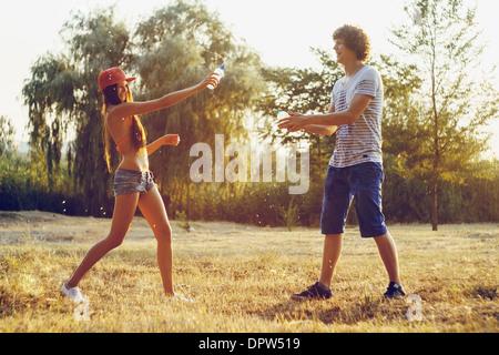 Garçon et fille des éclaboussures de l'eau en bouteille pendant l'été fun in the park