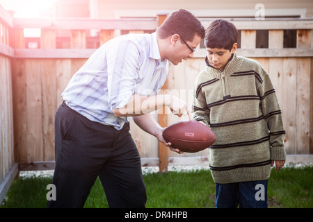 Hispanic father teaching son to play football Banque D'Images