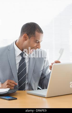 Jeune homme crier dans le téléphone au bureau Banque D'Images