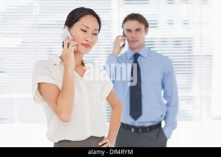 L'homme d'affaires et l'utilisation de téléphones cellulaires dans office Banque D'Images