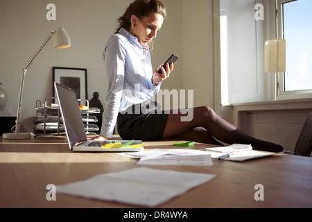Attractive young businesswoman sitting sur son bureau dans un bureau moderne à la recherche de son téléphone intelligent. Banque D'Images