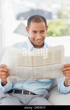 Happy businessman reading newspaper sur canapé Banque D'Images