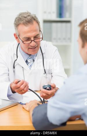 Smiling doctor en tenant ses patients hypertension Banque D'Images