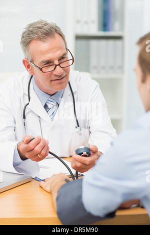Smiling mature médecin prenant ses patients hypertension Banque D'Images