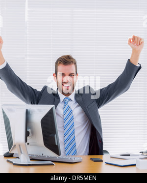 Cheerful businessman clenching fist at office desk Banque D'Images