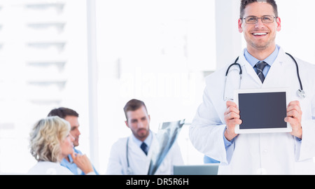 Doctor holding digital tablet with colleagues in meeting Banque D'Images