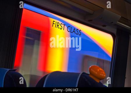 Signe de première classe sur la fenêtre de transport ferroviaire avec train brouillée derrière UK Banque D'Images