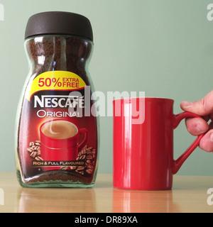 Pot de Nescafé Café instantané d'origine caucasienne et la main de l'homme de ramasser une tasse rouge PARUTION Banque D'Images
