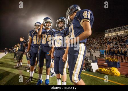 Joueurs de football de l'école secondaire sur la touche talk pendant un jeu de nuit à San Juan Capistrano, CA. Banque D'Images