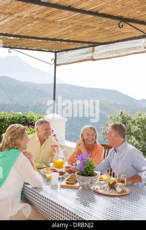 Les couples de prendre le petit-déjeuner sur un balcon avec vue sur montagne Banque D'Images