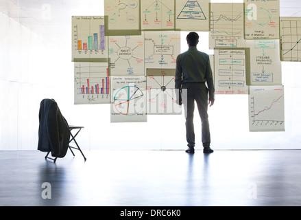 Man graphiques et tableaux sur verre wall in office Banque D'Images