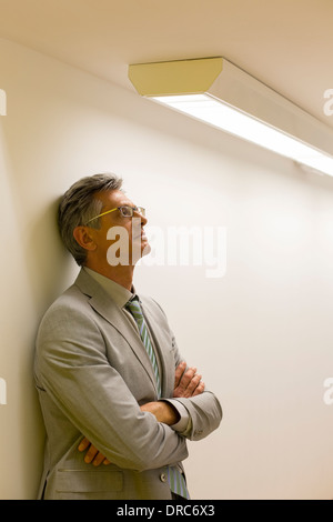 Businessman leaning against office wall Banque D'Images