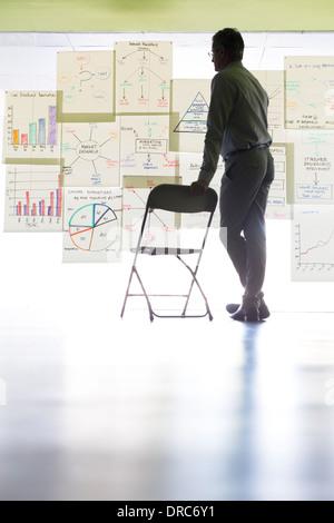 Businessman affichage des tableaux et des graphiques sur office wall Banque D'Images