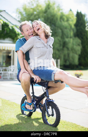 Petit couple riding bicycle in grass