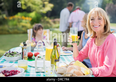 Smiling woman enjoying lunch at table in backyard Banque D'Images
