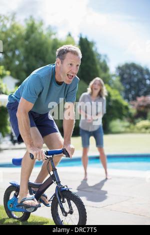 Petites Man riding bicycle at poolside