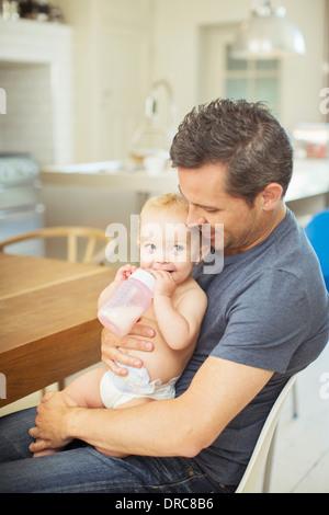 Père nourrir bébé dans la cuisine Banque D'Images