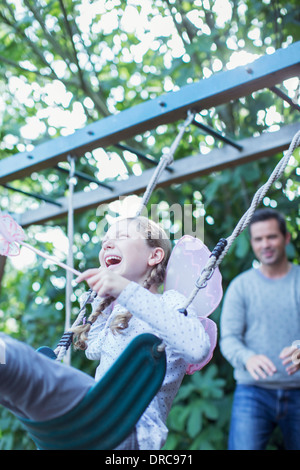 Père fille poussant sur swing en plein air Banque D'Images