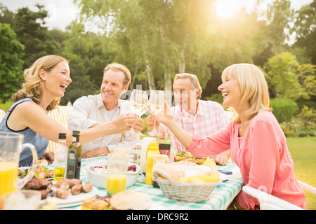 Des couples toasting wine glasses at table in backyard Banque D'Images