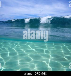 Vue fractionnée de déferlement des vagues de l'océan et sous la lumière du soleil sur le fond de sable Banque D'Images