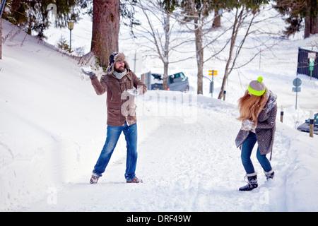 Couple Having Snowball Fight, Bavière, Allemagne, Spitzingsee Banque D'Images