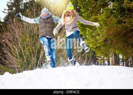 Saut dans la neige, couple, Spitzingsee Bavaria, Allemagne Banque D'Images