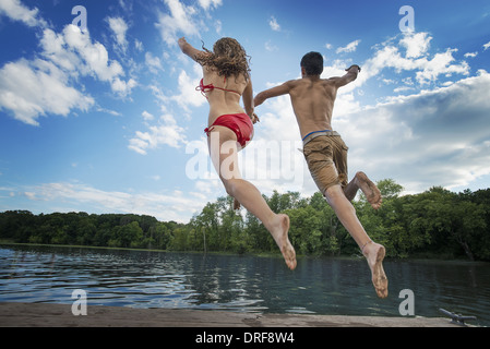 L'état de New York USA boy and girl leaping off jetty en lac rivière Banque D'Images