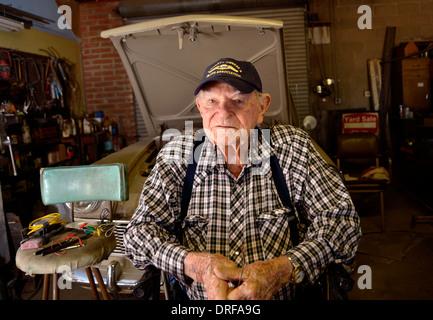 A 93 ans, l'homme dans son garage, où il travaille sur les voitures. Banque D'Images