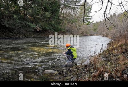 Jeune garçon de pêche sur une berge Banque D'Images