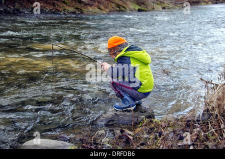 Jeune enfant prétendant à pêcher au bord de la rivière Banque D'Images