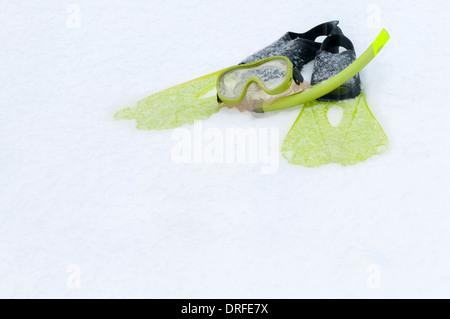 Tuba, masque et palmes allongé sur la neige Banque D'Images