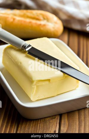 Cube de beurre à l'aide d'un couteau sur la table en bois Banque D'Images
