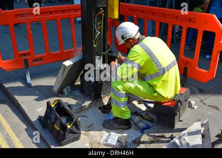 Electrician working sur les câbles à la base de la colonne d'éclairage de rue Banque D'Images