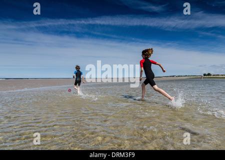 Royaume-uni, Ecosse, Burghead Bay, les enfants courent dans l'eau Banque D'Images