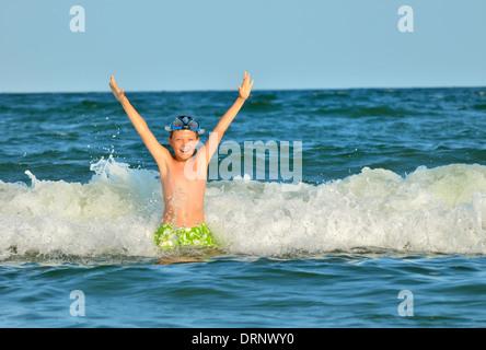 Garçon à la mer à jouer dans les vagues Banque D'Images