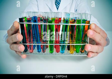 L'homme en blouse blanche avec des tubes à essai avec des liquides de différentes couleurs dans un laboratoire Banque D'Images