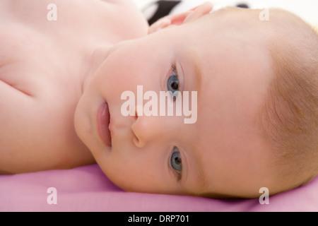 Bond petit bébé yeux bleus se trouvant dans détendue lit rose Banque D'Images