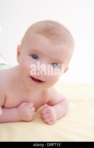 Peu d'yeux bleus de bébé couché sur lit jaune lumière smiling Banque D'Images