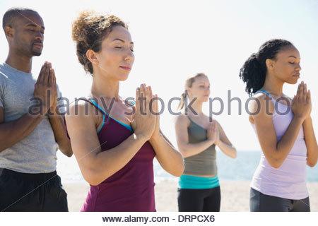 Groupe exécutant yoga on beach Banque D'Images