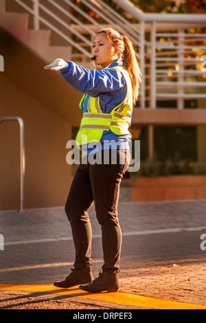 Un officier de police américain asiatique dirige le trafic sur le campus de l'Université de Californie à Irvine. Banque D'Images