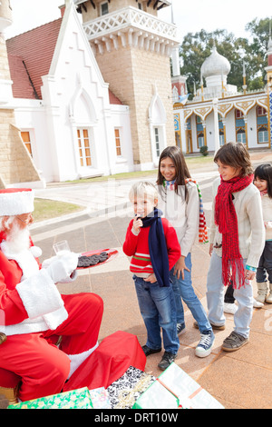 Père Noël offrant aux enfants des biscuits Banque D'Images