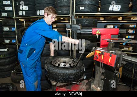 Un mécanicien de voiture s'adapte à un nouveau pneu sur une jante. Banque D'Images