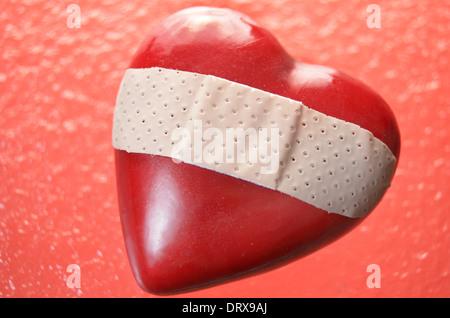 Coeur avec bandage sur fond de verre ondulé rouge Banque D'Images