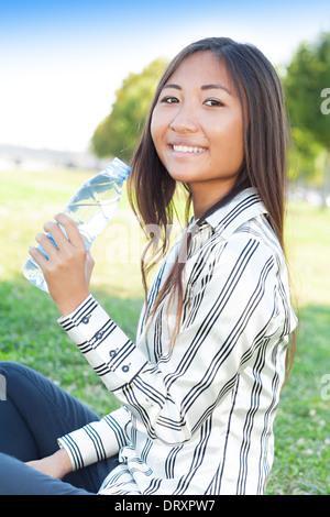 Portrait d'une jeune fille asiatique dans un parc avec une bouteille d'eau Banque D'Images